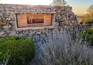 Holiday Inn Club Vacations David Walley's Resort wooden property sign surrounded by stone decor