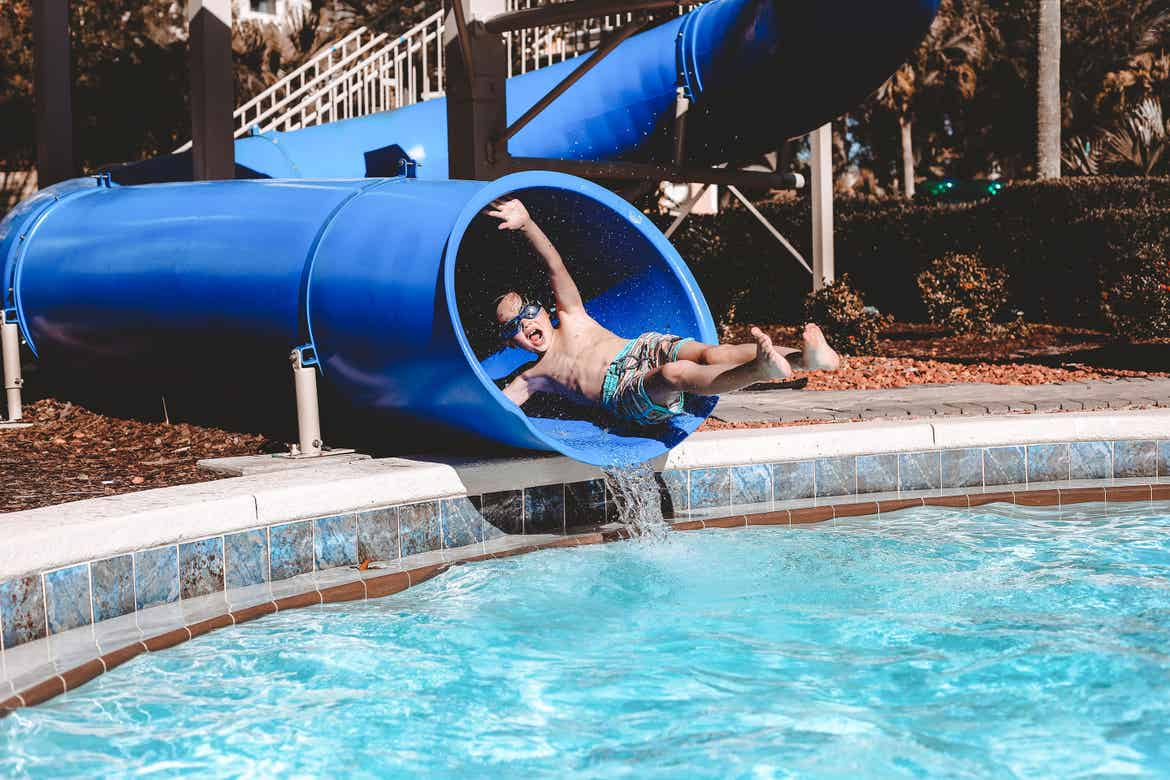 Grey wears swim trunks and goggles as he emerges from a blue water slide at River Island.