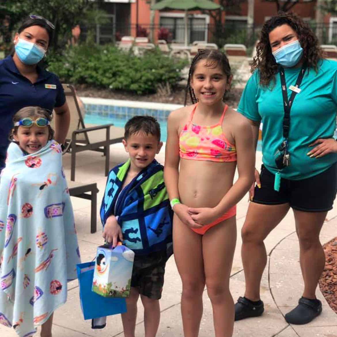 Featured Member, Sara Perezes family stands with two masked HICV Team Members outside of our River Island pool.