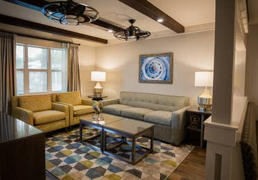 Living room with a couch and two chairs in a two-bedroom Signature Collection villa at Cape Canaveral Beach Resort.