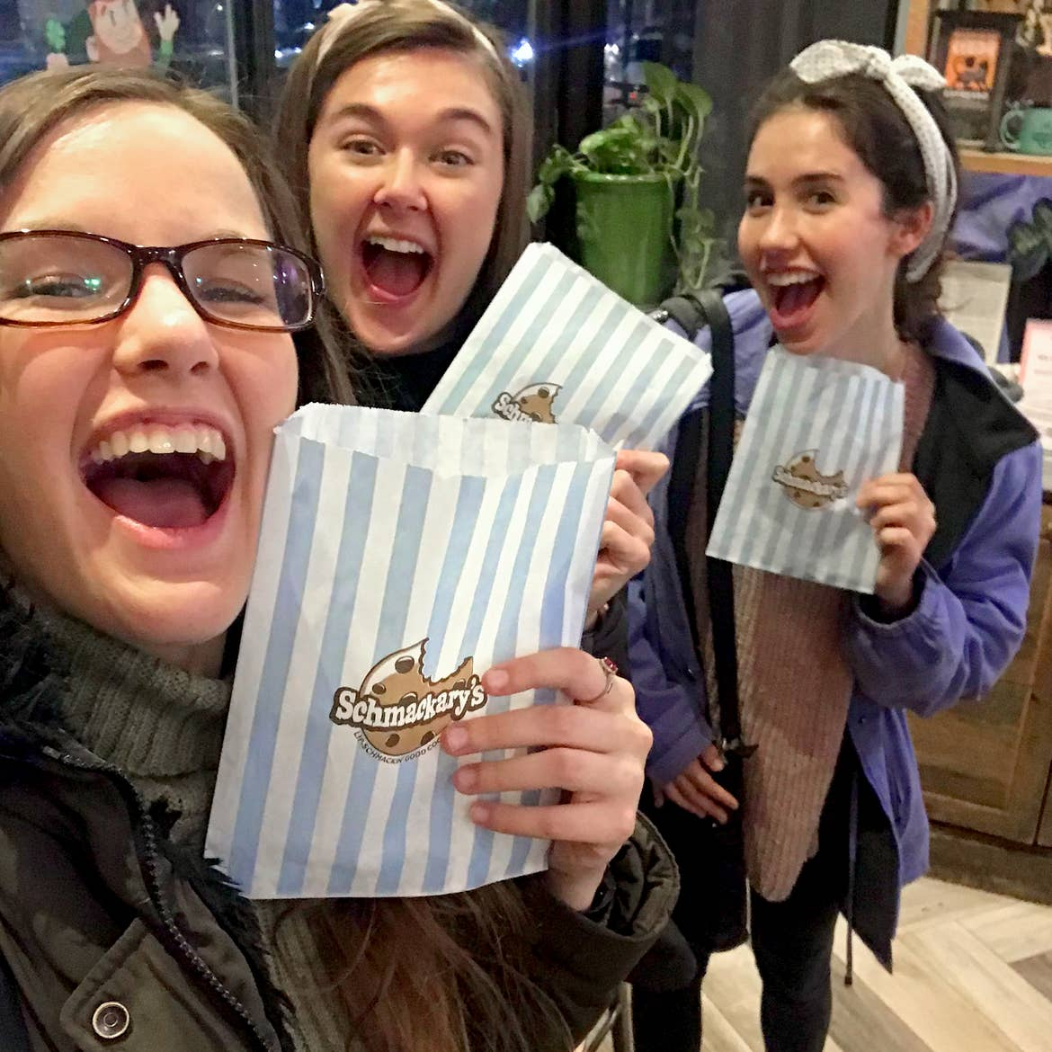 Three caucasian women in winter jackets hold a wax paper with blue and white stripes from 'Schmackary's ' in New York City.