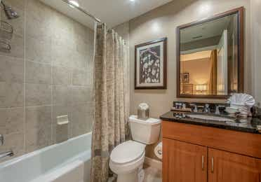 Bathroom with shower/tub combination, sink with mirror, and toilet in a three-bedroom villa at Sunset Cove Resort in Marco Island, Florida