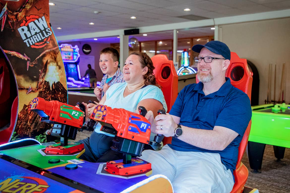 A caucasian man (right) wearing a navy baseball cap and polo is seated next to a caucasian woman (left) wearing a light blue t-shirt in an arcade gaming seat behind shooters as a tween boy (back-left) watches from behind the seat.
