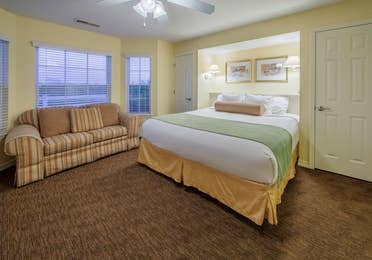 Bedroom with bed, couch, and three large windows in a Presidential two-bedroom villa at Ozark Mountain Resort in Kimberling City, Missouri