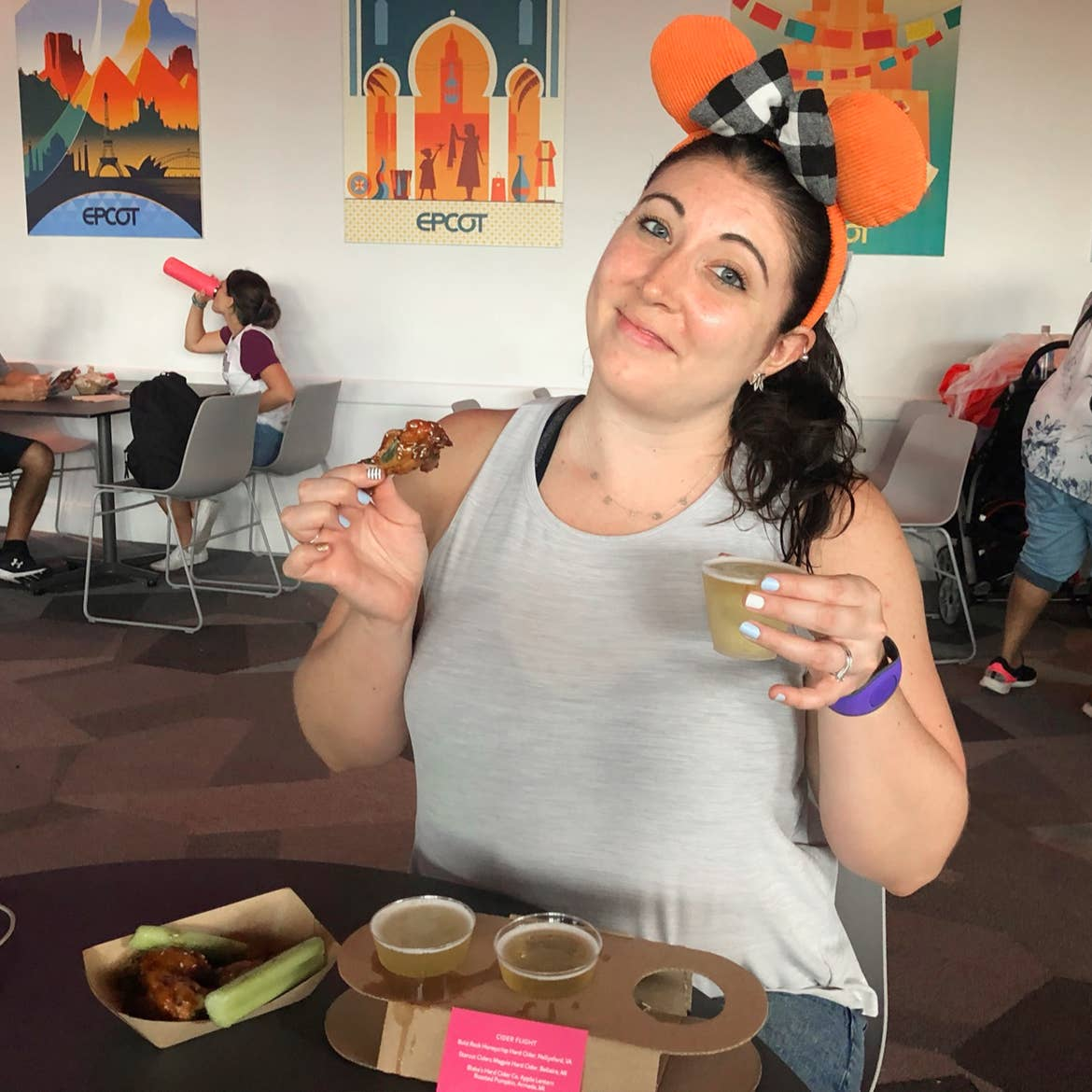 A caucasian woman wearing orange Mickey ears and a grey tank top holds a chicken thigh in her right hand, and cider in her left hand indoors.
