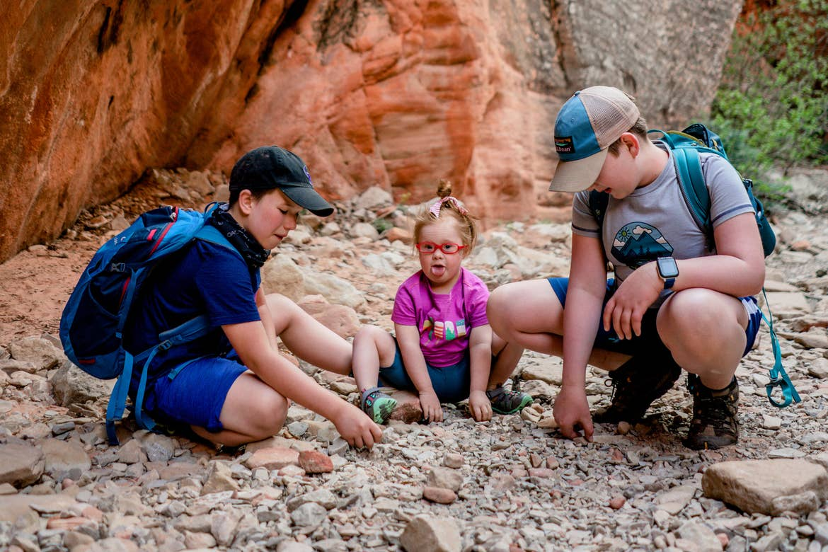 Featured Contributor, Melody Forsyth's two sons (left and right) sit with daughter, Ruby (middle) in front of a rock formation touching stones while wearing hiking backpacks.