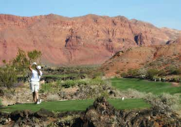 Person on a golf course and swinging a golf club with a desert mountain range in the background
