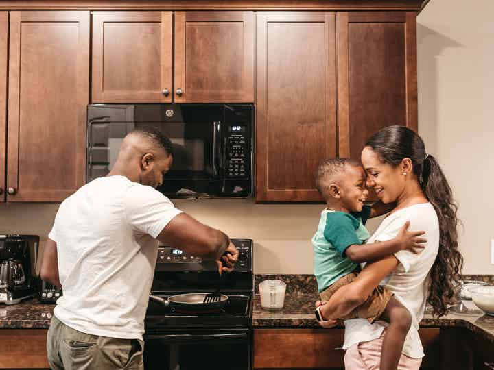 Woman holding a small child in their kitchen while a man prepares food on the stove