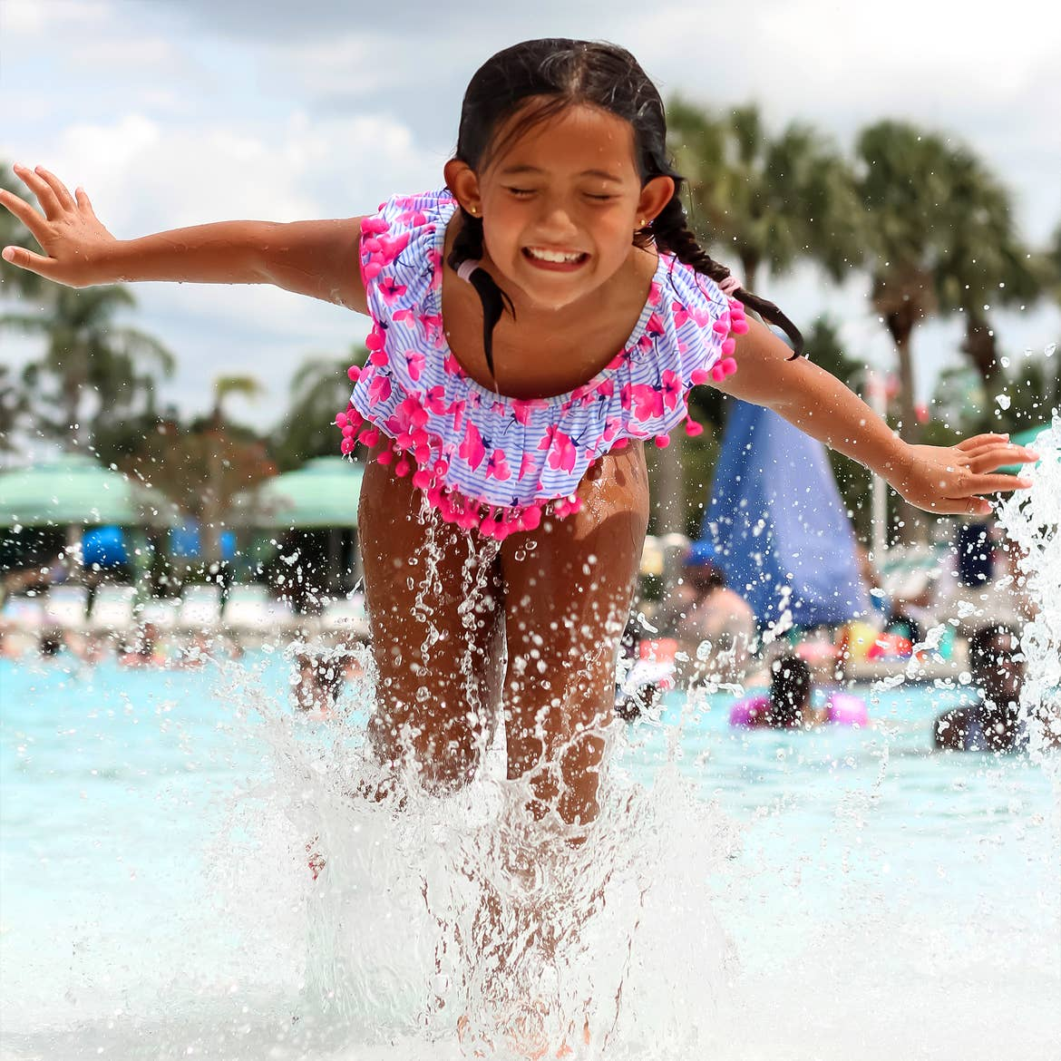 An Asian girl wearing a pink, striped swimsuit splashed in the zero-entry pool at our Orange Lake Resort located in Orlando, Florida.