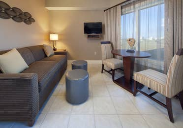 Living room with couch, flat screen TV, and large window with seating area in a two-bedroom villa at Galveston Beach Resort