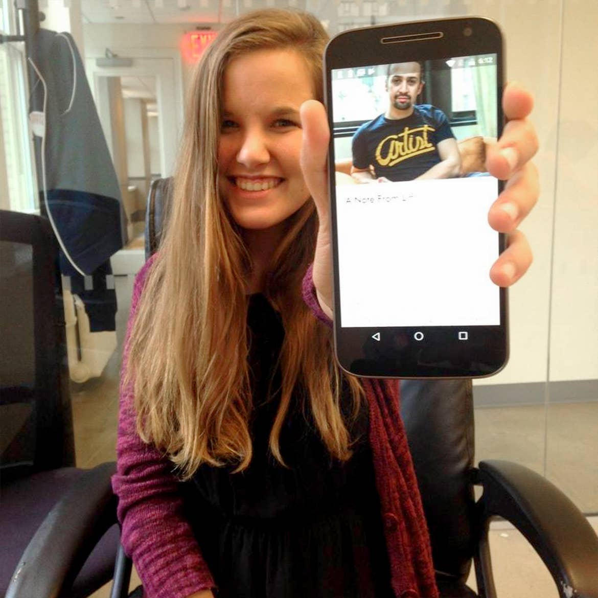 A caucasian woman with long ash-blonde hair wears a red cardigan while holding a mobile device with a picture of Lin Manuel-Miranda for the 'Hamilton' Ticket Lottery.