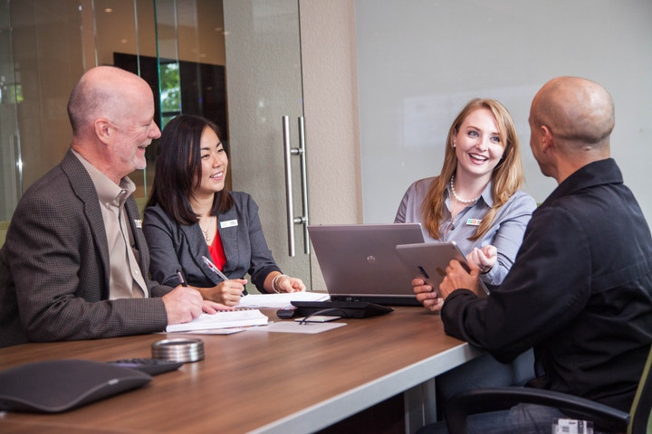 Four business professionals sitting around a conference table
