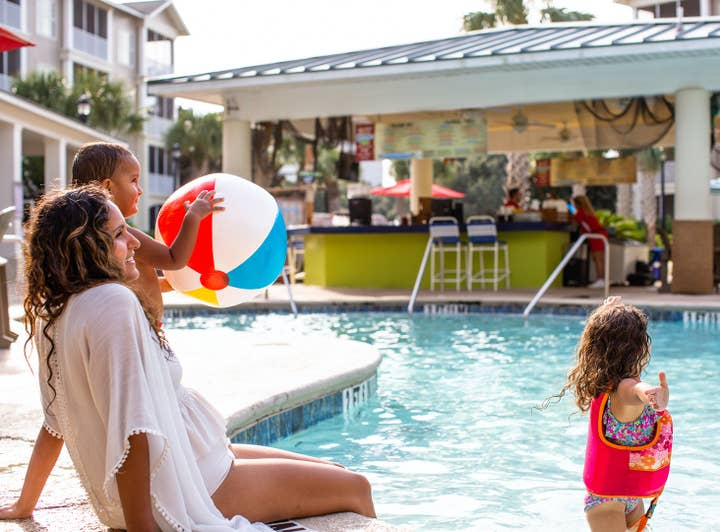 Mother with two children sitting on edge of outdoor pool at South Beach Resort in Myrtle Beach, South Carolina.