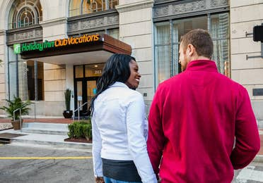 Sally Butan (left) of @butanclan and her husband cross the street towards our New Orleans resort with signage that reads, 'Holiday Inn Club Vacations.'