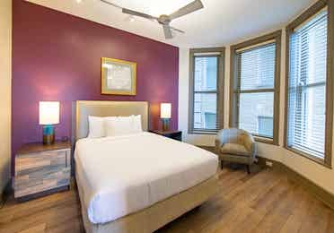 One bedroom villa with bed, three windows and ceiling fan at New Orleans Resort in Louisiana.