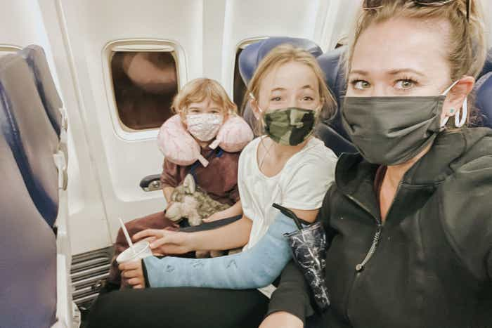 The Haby girls sit near a window seat while wearing masks on an airplane.