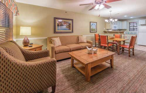 Living room, dining table, and kitchen in a two-bedroom villa at Fox River Resort in Sheridan, Illinois