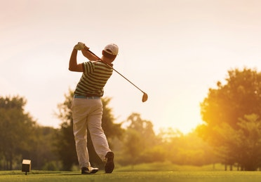 Man swinging a golf club with sun setting in the background