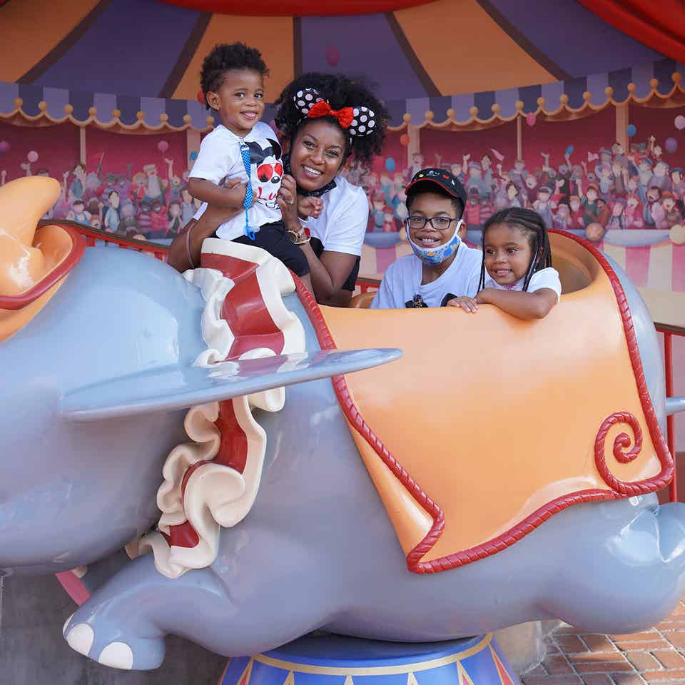 Featured Contributor, Tina Meeks, poses with her daughter and sons on a Dumbo ride vehicle located in Magic Kingdom at Walt Disney World resort.