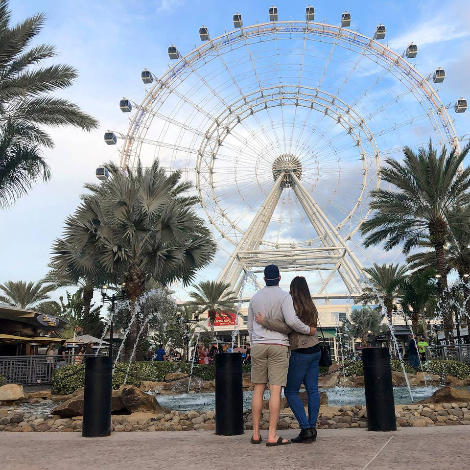 Featured contributor, Tori Ferrante (right) and her husband embrace in front of the Orlando Icon Ferris Wheel at ICON park under a blue sky.