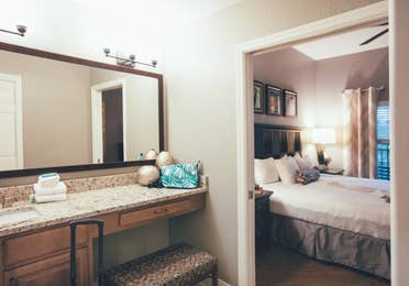 Bathroom with sink and large mirror with view of bedroom in the background in a one bedroom villa in North Village at Orange Lake Resort near Orlando, Florida