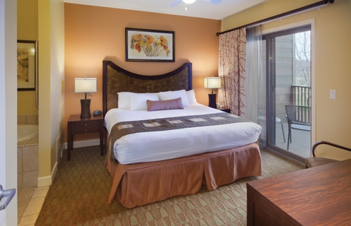 Master bedroom with attached bathroom and access to furnished balcony in a one-bedroom villa at Lake Geneva Resort