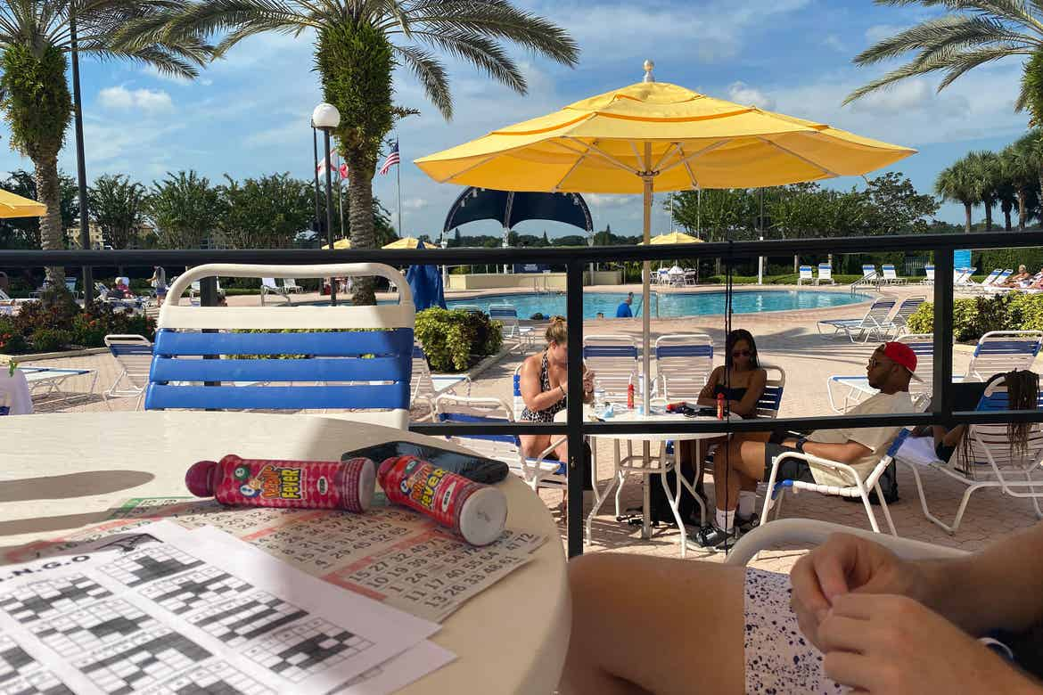 guests sit under a yellow umbrella playing bingo near the River Island pool at our Orange Lake resort in Orlando, Florida.