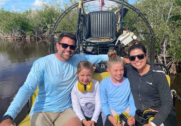 A caucasian woman (left) wearing sunglasses and a black zip-up hoodie, two caucasian girls (middle) and a caucasian male (right) wearing sunglasses and a blue long-sleeve shirt sit on an airboat in the Everglades.