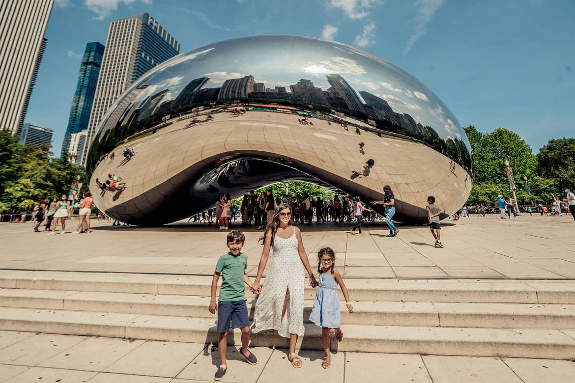 A woman (middle) holding a young boy (left) and young girls (right) hand at cloud gate in Chicago.