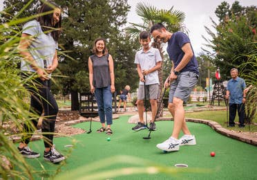 Five guests playing outdoor mini golf at Villages Resort in Flint, Texas.