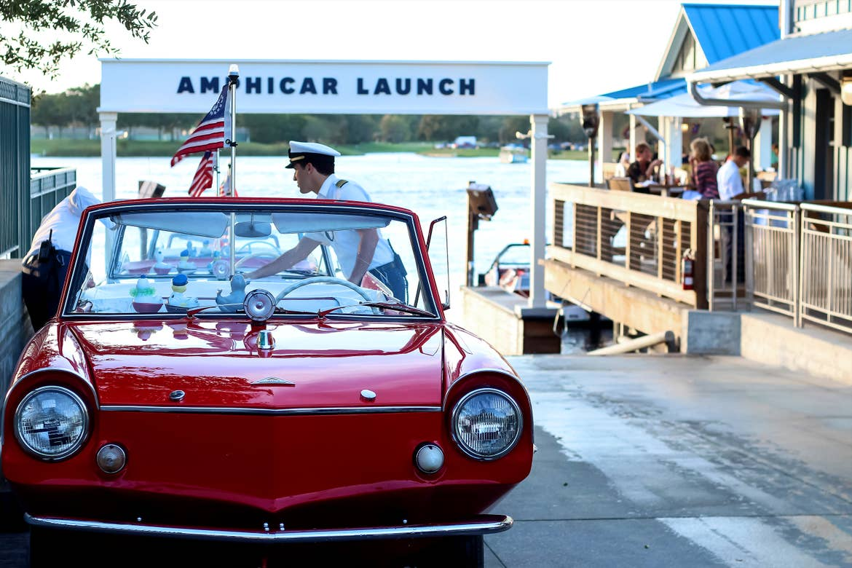 A Caucasian man wearing Nautical Captain attire preps a red, amphibious car on the launch pad near a white sign that reads, 'Amphicar Launch.'