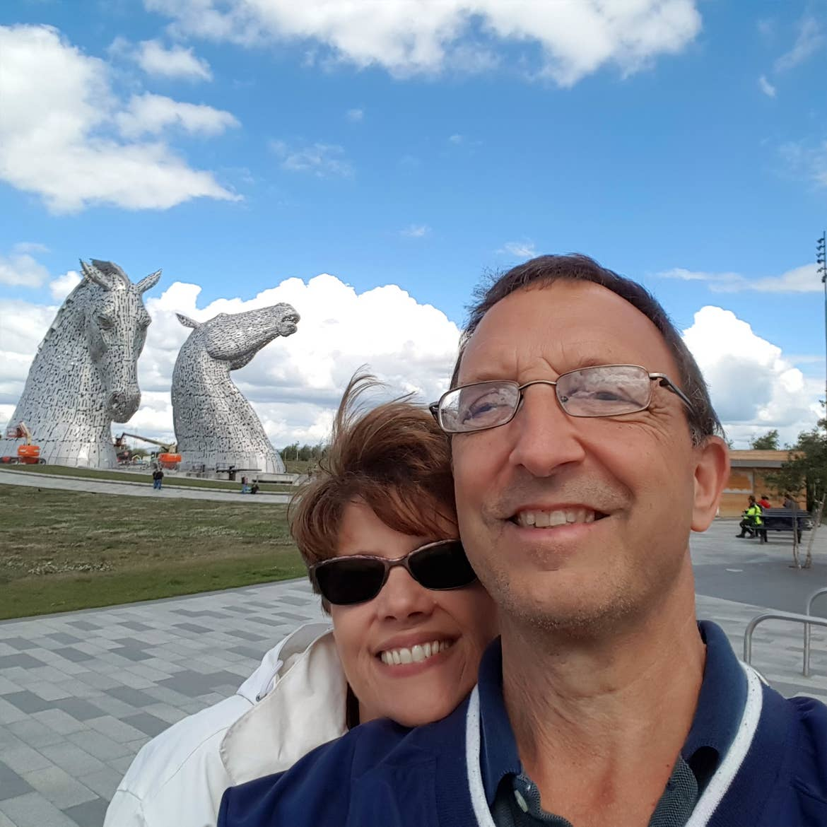 A caucasian man (right) wearing a navy windbreaker and a caucasian woman (left) standing behind him in a white windbreaker jacket stand in front of the Kelpies in Falkirk, Scotland.