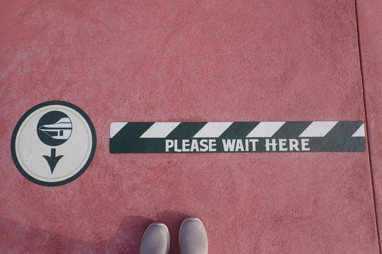 A COVID-19 safety queue decal at Walt Disney World resort indicating social distancing.