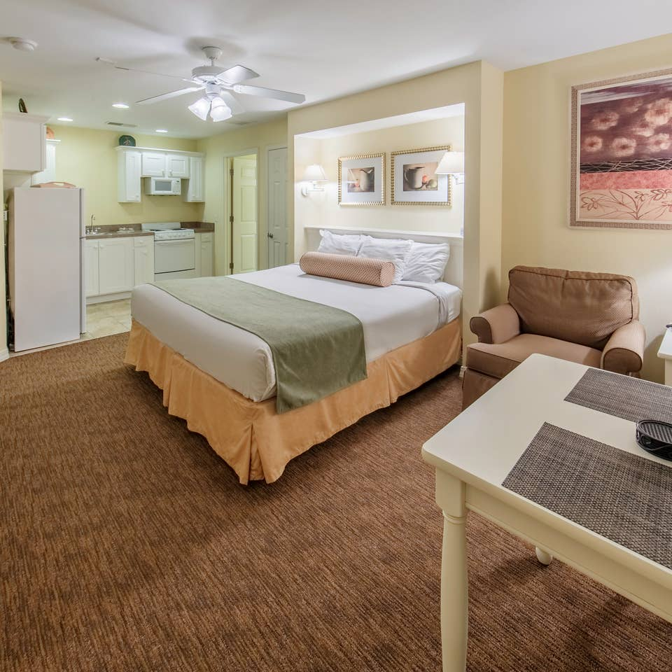 Bedroom with seating area, kitchenette, and flat screen TV in a Presidential two-bedroom villa at Ozark Mountain Resort in Kimberling City, Missouri