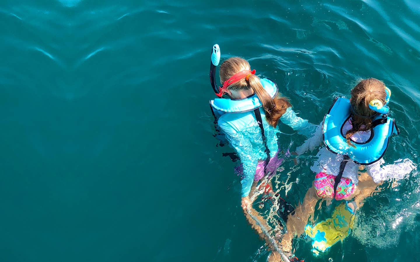 Featured Contributor, Chris Johnston's two daughters, Kyler (right) and Kyndall (left), wear multi-colored snorkel gear while holding onto a rope in the ocean.