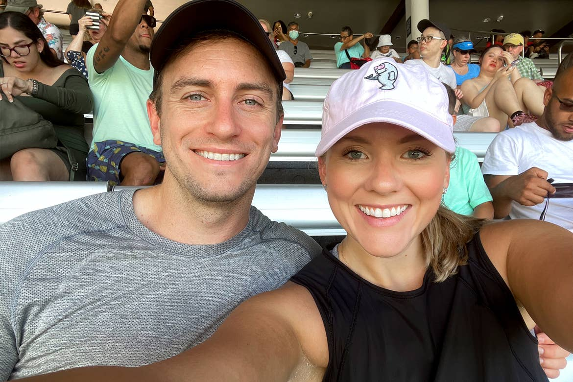 A Caucasian male wearing a grey t-shirt, black cap (left) and a Caucasian female wearing a pink baseball cap and black tank top (right) sit in bleachers in SeaWorld Orlando.