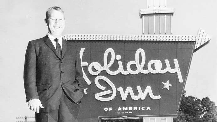 Kemmons Wilson standing in front of a Holiday Inn sign in the early 1970s