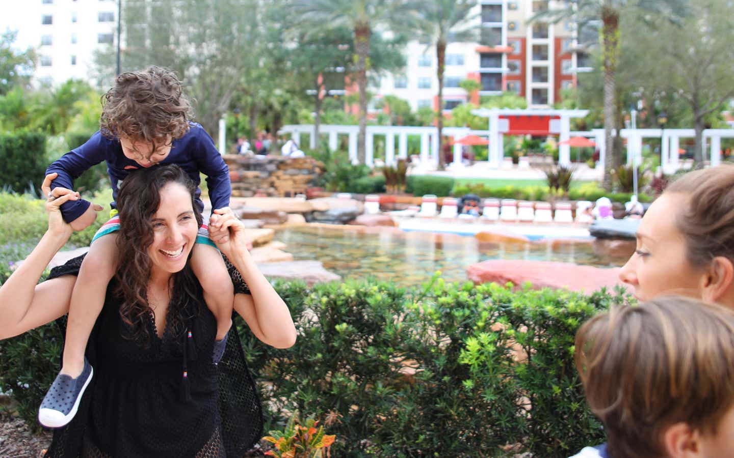 Young child on shoulders of mom exploring River Island at Orange Lake Resort near Orlando, Florida