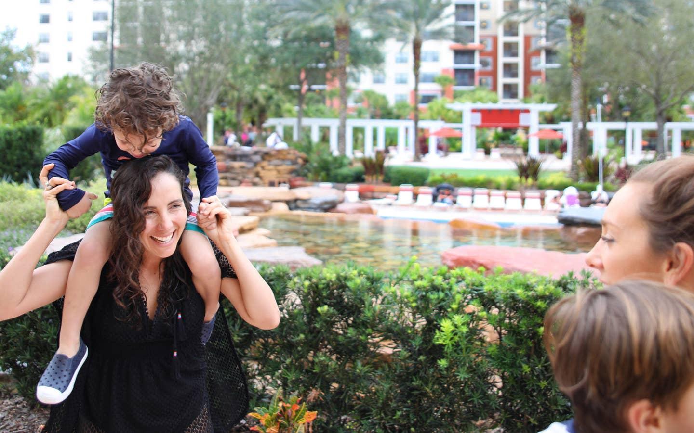 Young child on shoulders of mom exploring River Island at Orange Lake Resort near Orlando, Florida