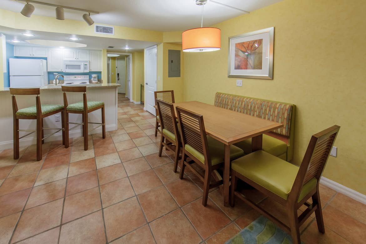 Dining room table with six chairs and two bar stools at the kitchen counter in a two-bedroom lock-off villa at Cape Canaveral Beach Resort