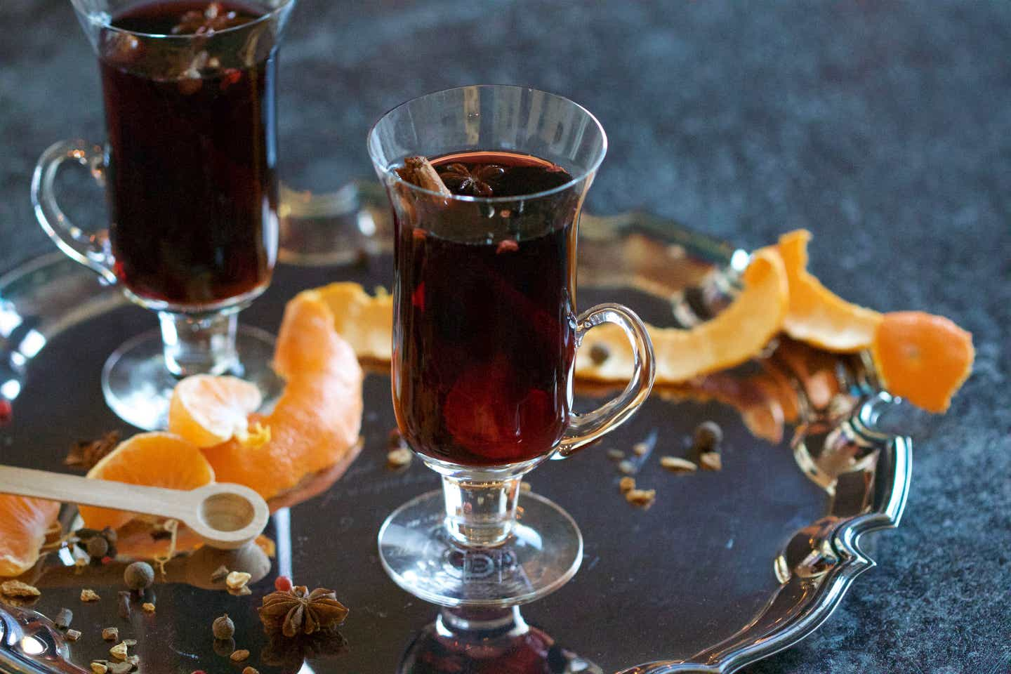 Mulled wine served in a glass mug surrounded by orange peel spirals on top of a silver serving platter.