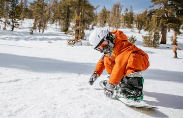 A boy wearing orange snow jacket, pants and white helmet makes his way down a snowy slopes on a snowboard.