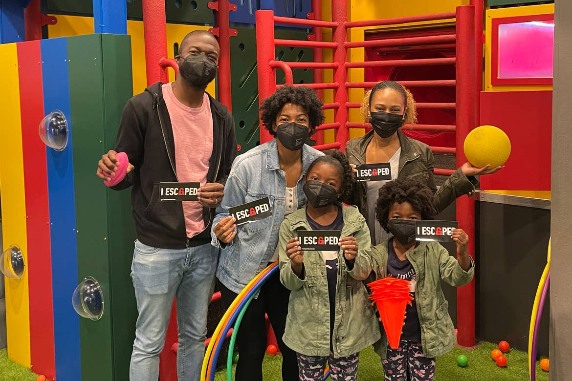 Monet (center) and her family wear safety masks while holding stickers that read, 'I escaped' at The Escape Game on International Drive.