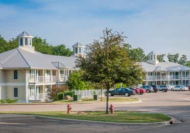 Outdoor property buildings and parking lot surrounded by trees at Fox River Resort in Sheridan, Illinois