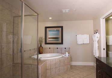 Bathroom with soaking tub, walk-in shower, and complimentary robes in a four bedroom Signature villa in River Island at Orange Lake Resort near Orlando, Florida