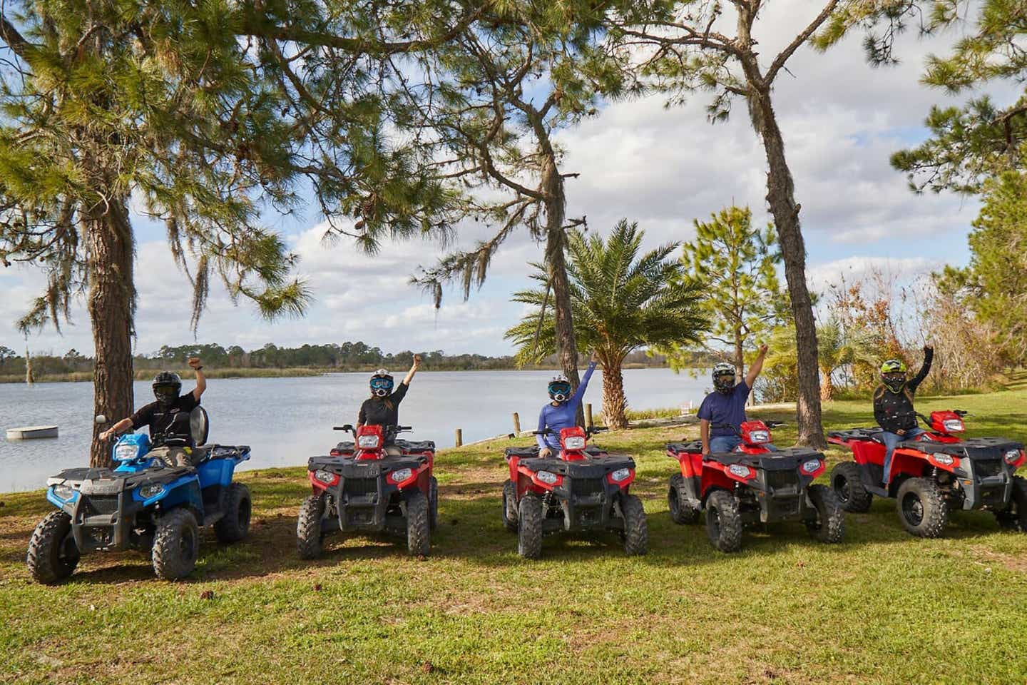 Five people sitting on ATVs