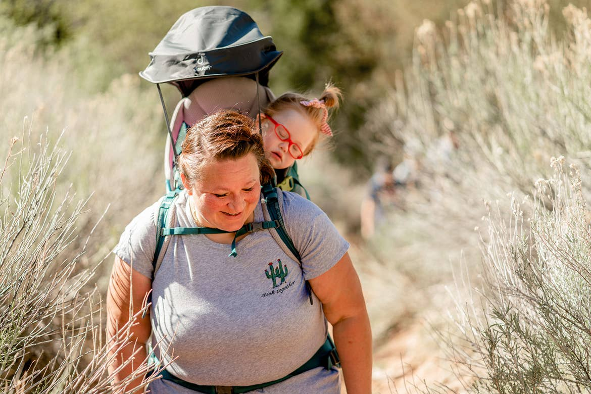 Featured Contributor, Melody Forsyth (left), backpacks with her daughter, Ruby (right), as they walk through some wild plants.