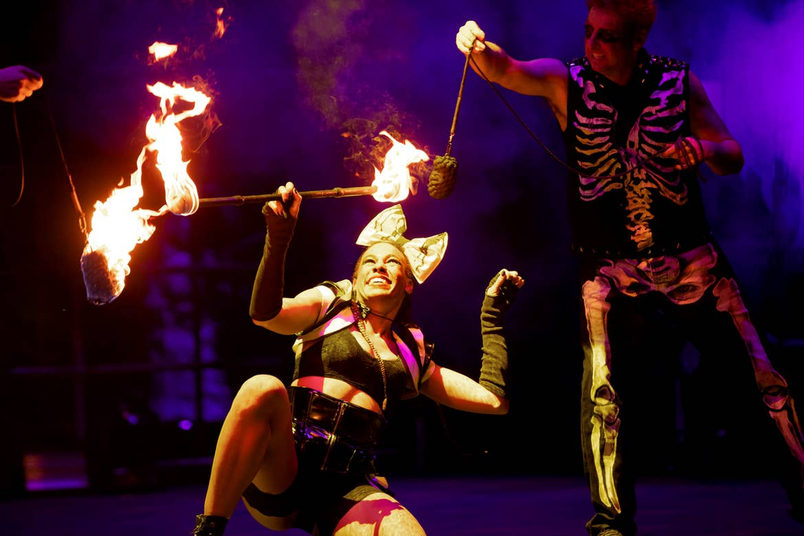 A woman and man perform with fire onstage.