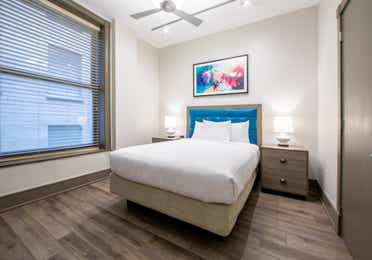 Two bedroom villa bedroom with bed, ceiling fan and large window at New Orleans Resort in Louisiana.
