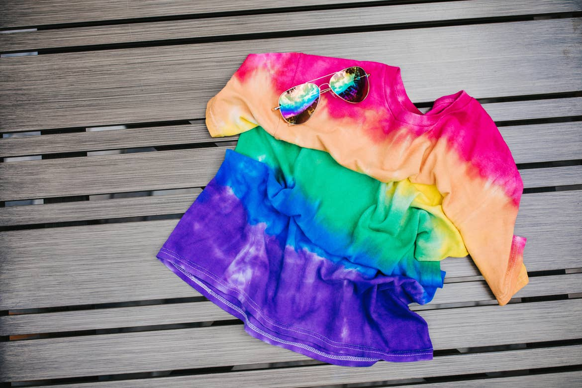 A tie-dyed shirt placed on a wood slatted table with a pair of sunglasses.
